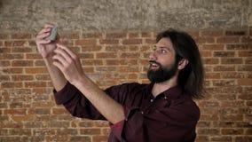 Den unga attraktiva brunettmannen med skägget gör videoen på smartphonen som omkring bedrar, tegelstenbakgrund, kommunikation stock video