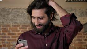 Den unga attraktiva brunettmannen med skägget håller ögonen på i smartphonen som stoppar hår, tegelstenbakgrund, kommunikation stock video