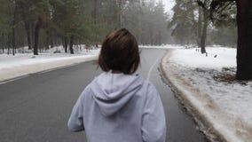 Den unga attraktiva Caucasian flickan som k?r i det sn?ig, parkerar i vinter med h?rlurar Slutet upp baksida f?ljer skottet stock video