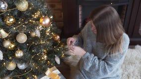 Den unga attraktiva caucasian kvinnan dekorerar julgranen vid guld- bollar, julhelgdagsaftonen, x-mas ordningar, girlander och stock video