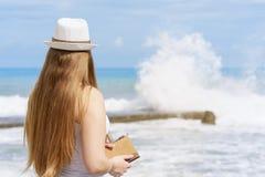 Den unga attraktiva europeiska kvinnan med notepaden och pennan blir nästan stranden av det blåa tropiska havet på bakgrund av de royaltyfria bilder