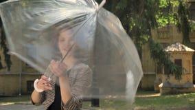 Den unga attraktiva flickan öppnar och rotera paraplyet parkerar in i dag, i sommar som håller ögonen på på kameran stock video