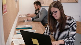 Den unga attraktiva flickan använder en bärbar dator och att arbeta med dokument som gör anmärkningar i det moderna startup konto Arkivfoton