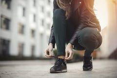 Den unga attraktiva flickan binder skosnöre arkivfoto