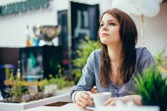 Den unga attraktiva flickan dricker kaffe i ett stadskafé royaltyfri foto