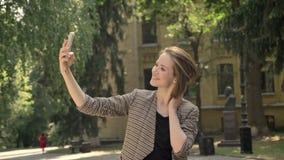 Den unga attraktiva flickan gör selfie parkerar in i dag, i sommar, rörande hår, kommunikationsbegrepp stock video