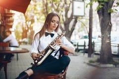 Den unga attraktiva flickan i den vita skjortan med en saxofon som sitter nära caffe, shoppar - utomhus- i sity Sexig ung kvinna  Arkivbild