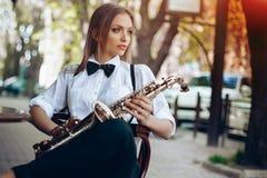 Den unga attraktiva flickan i den vita skjortan med en saxofon som sitter nära caffe, shoppar - utomhus- i sity Sexig ung kvinna  Royaltyfri Bild