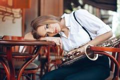 Den unga attraktiva flickan i den vita skjortan med ett saxofonsammanträde på caffe shoppar - utomhus- i gata Sexig ung kvinna me Royaltyfri Fotografi