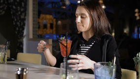 Den unga attraktiva flickan i stången som talar till bartendern, dricker den exklusiva coctailen lager videofilmer