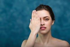 Den unga attraktiva flickan med svart hår som bakom fixas, stora ögon, tjocka ögonbryn och nakna skuldror som rymmer handen nära, Fotografering för Bildbyråer