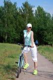 Den unga attraktiva flickan rider en cykel i sommaren Sportlivsföring Arkivfoton