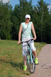 Den unga attraktiva flickan rider en cykel i sommaren Sportlivsföring Royaltyfria Foton