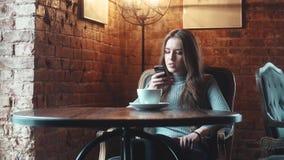 Den unga attraktiva flickan sitter i ett hemtrevligt kafé och använder en mobiltelefon lager videofilmer