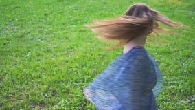 Den unga attraktiva flickan snurrar hår i parkeracloseupen långsam rörelse stock video