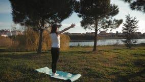 Den unga attraktiva flickan som gör övningar, lägger och sträcker på en matt yoga parkerar in Sunt aktivt begrepp lager videofilmer