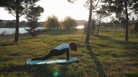 Den unga attraktiva flickan som g?r ?vningar, l?gger och str?cker p? en matt yoga parkerar in Sunt aktivt begrepp stock video