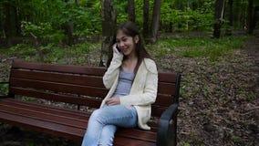 Den unga attraktiva flickan talar till telefonen på bänk oklarheter över vita parksommartrees leende Kamera för statisk elektrici stock video