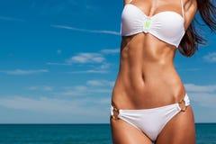 Den unga attraktiva flickan tycker om sommardag på stranden Royaltyfria Bilder
