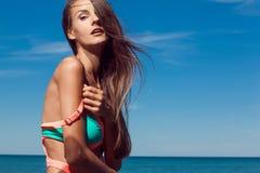 Den unga attraktiva flickan tycker om sommardag på stranden Fotografering för Bildbyråer