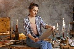 Den unga attraktiva konstnären i kursen av teckningen beräknar en blick det gjorda arbetet Hon drar olja- och akrylmålarfärger Royaltyfri Foto