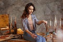 Den unga attraktiva konstnären i kursen av teckningen beräknar en blick det gjorda arbetet Hon drar olja- och akrylmålarfärger arkivbilder