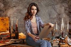 Den unga attraktiva konstnären i kursen av teckningen ser framåtriktat på en bild som hon målar med bilden henne Arkivfoton