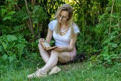 Den unga attraktiva kvinnaläseboken under trädet parkerar in på den soliga dagen Royaltyfri Foto