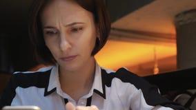 Den unga attraktiva kvinnan använder hennes mobiltelefon i en hemtrevlig kaférestaurang Hon är förvånad och ilsken arkivfilmer