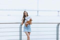 Den unga attraktiva kvinnan går med hunden på havspromenad arkivfoto