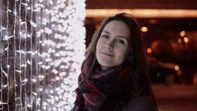 Den unga attraktiva kvinnan i den fallande snön på julnatten som ser kameran, tänder på bakgrund Arkivfoto