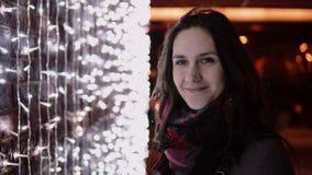 Den unga attraktiva kvinnan i den fallande snön på julnatten som ser kameran, tänder på bakgrund fotografering för bildbyråer