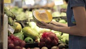 Den unga attraktiva kvinnan i en supermarket väljer frukterna och grönsakerna stock video