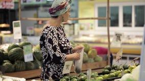 Den unga attraktiva kvinnan i en supermarket väljer frukterna och grönsakerna lager videofilmer