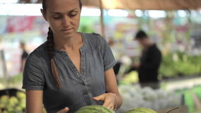 Den unga attraktiva kvinnan i en supermarket väljer frukterna och grönsakerna arkivfilmer