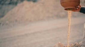Den unga attraktiva kvinnan i etnisk klänning sitter nära vägen och häller sand ut ur kannan Vattnet vände in i sand lager videofilmer
