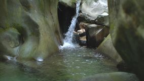 Den unga attraktiva kvinnan i ultrarapid sätter hennes händer under strömmen av den lilla vattenfallet i bergsjön i gräsplan arkivfilmer