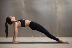 Den unga attraktiva kvinnan i uppåtriktad planka poserar, den gråa studiobackgroen Royaltyfria Bilder