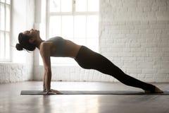Den unga attraktiva kvinnan i uppåtriktad planka poserar, vit studiobackgr Royaltyfria Foton