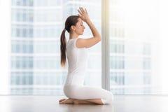 Den unga attraktiva kvinnan i vajrasana poserar mot golvfönster Arkivfoto