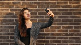 Den unga attraktiva kvinnan med exponeringsglas tar en selfie som går runt om staden på solnedgången arkivfilmer