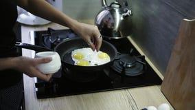 Den unga attraktiva kvinnan med den mörka badlakanet på hennes huvud förbereder frukosten för två Stekte ägg på pannan, flicka stock video
