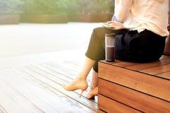 Den unga attraktiva kvinnan på parkerar och att arbeta med telefonen och att dricka kaffe och att ha lunch bråttom Affärsidéfoto Royaltyfria Foton