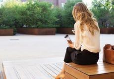 Den unga attraktiva kvinnan på parkerar och att arbeta med telefonen och att dricka kaffe och att ha lunch bråttom Affärsidéfoto Royaltyfria Bilder