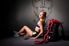 Den unga attraktiva kvinnan sitter på floren med sportutrustning Arkivbild
