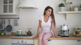 Den unga attraktiva kvinnan sitter på skrivbordet i hem- kök arkivfilmer