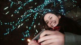 Den unga attraktiva kvinnan som använder smartphonen på det snöig anseendet för julnatten under ett träd, dekorerade med moussera Royaltyfri Bild