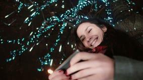Den unga attraktiva kvinnan som använder smartphonen på det snöig anseendet för julnatten under ett träd, dekorerade med moussera Arkivfoton
