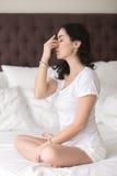 Den unga attraktiva kvinnan som gör omväxlande näsborreandning, poserar på Fotografering för Bildbyråer