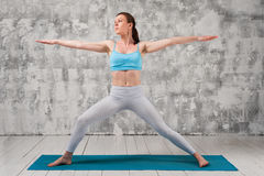 Den unga attraktiva kvinnan som gör yogakrigaren, poserar arkivbild